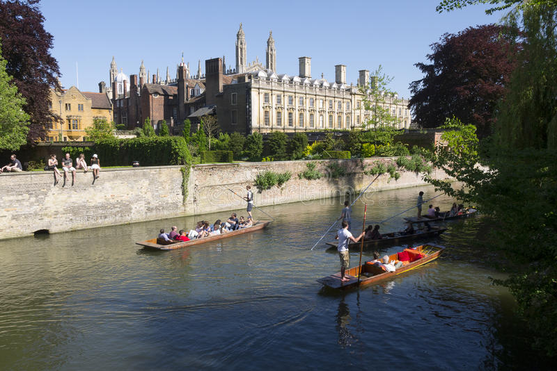 Punting on the River Cam Cambridge England UK. Punting on the River Cam in front of a Cambridge University college on a sunny afternoon in Cambridge England UK royalty free stock images