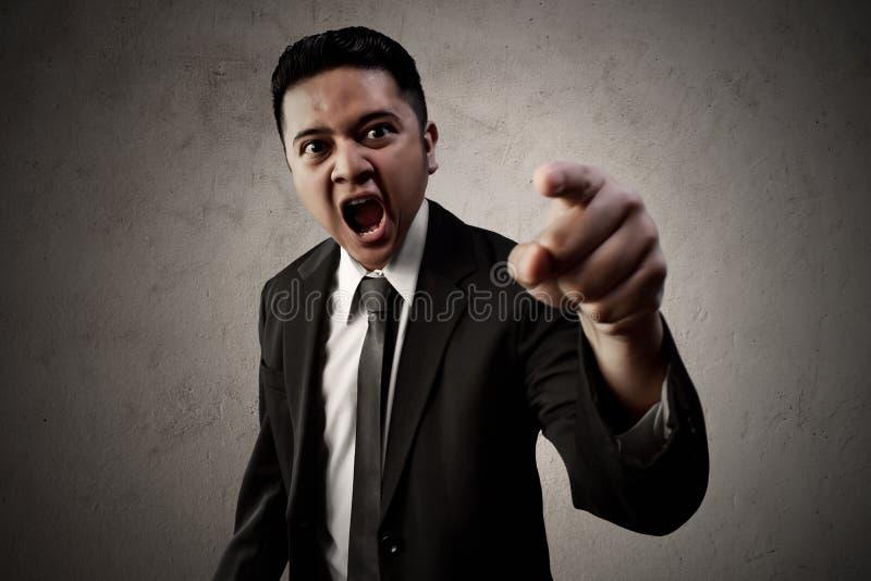 Punto asiatico arrabbiato dell'uomo di affari immagine stock