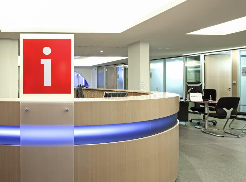 Punto de la información en el edificio de oficinas con la muestra plástica roja i escrito en ella imagen de archivo