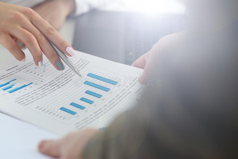 Punto di penna femminile dell'argento della tenuta del braccio nel grafico finanziario immagine stock