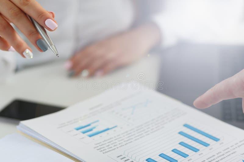 Punto di penna femminile dell'argento della tenuta del braccio nel grafico finanziario fotografie stock libere da diritti