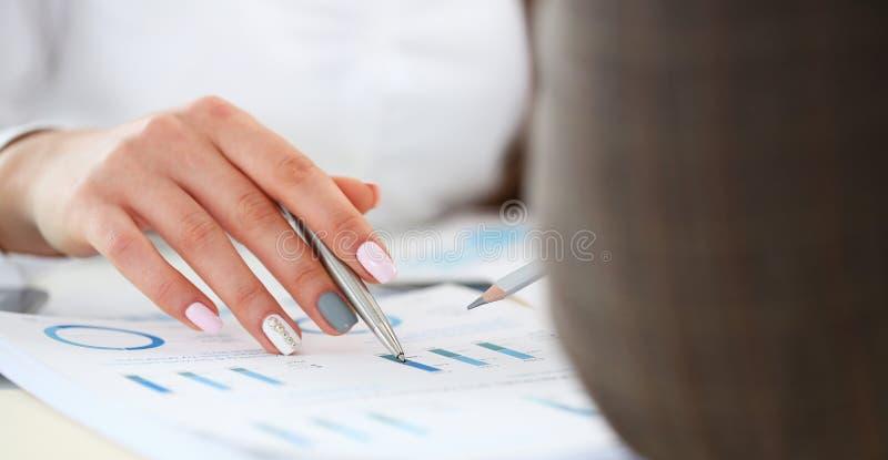 Punto di penna femminile dell'argento della tenuta del braccio nel grafico finanziario immagini stock