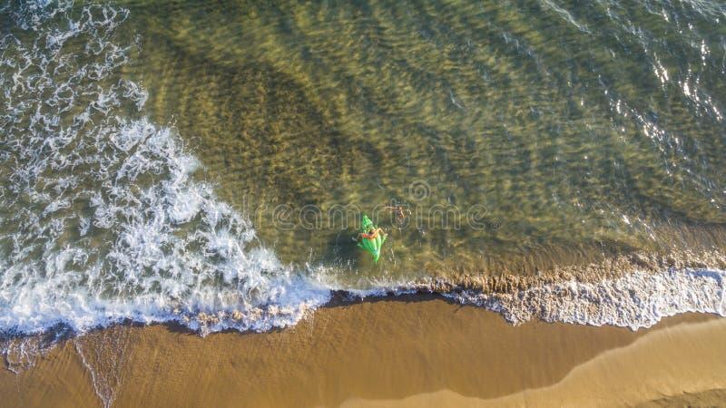 Punto di vista aereo del fuco dei bambini che giocano con un gonfiabile su una spiaggia e su un mare a Corfù Grecia immagini stock