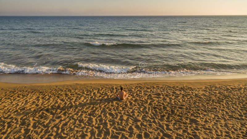 Punto di vista aereo del fuco di un uomo solo che si rilassa su una spiaggia calma appena prima il tramonto fotografie stock