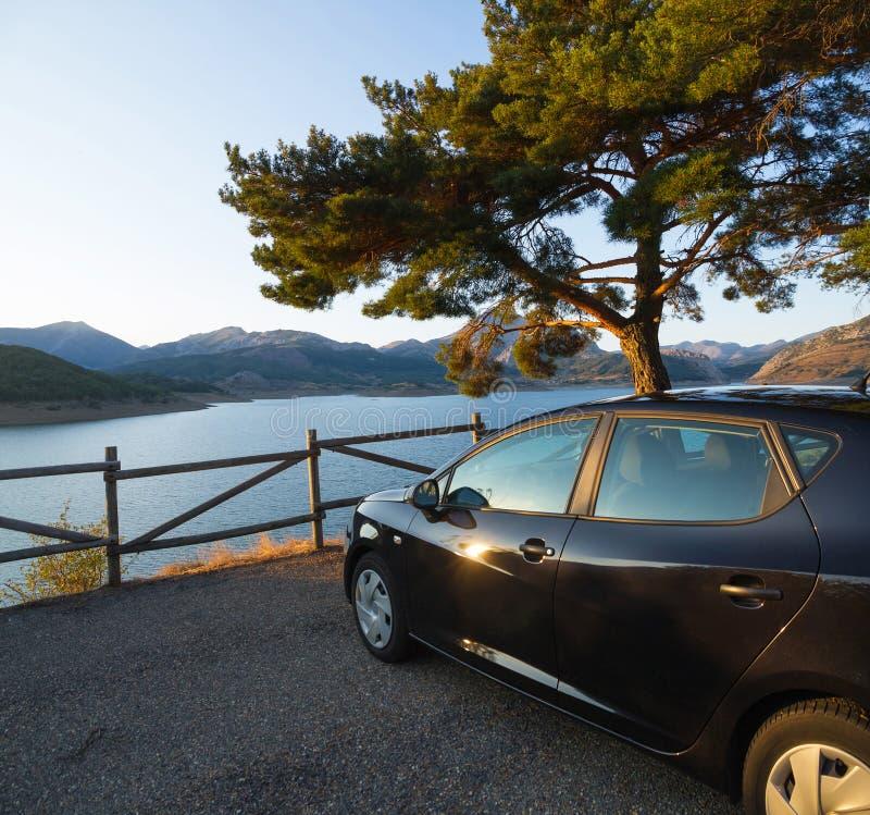 Punto di vista al tramonto Parcheggio davanti ad acqua ed al paesaggio delle montagne immagine stock libera da diritti
