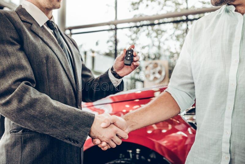 Punto di vista alto vicino del commerciante che fornisce chiave al nuovo proprietario e che stringe le mani nell'esposizione auto fotografia stock libera da diritti
