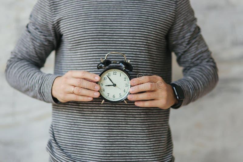 Punto di vista alto vicino dell'uomo che sta tenendo il vecchio orologio in sue mani fotografia stock libera da diritti