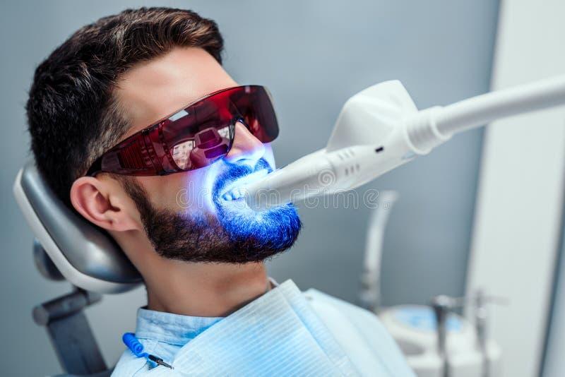 Punto di vista alto vicino dell'uomo che subisce il dente del laser che imbianca trattamento per rimuovere le macchie e scolorame immagine stock libera da diritti