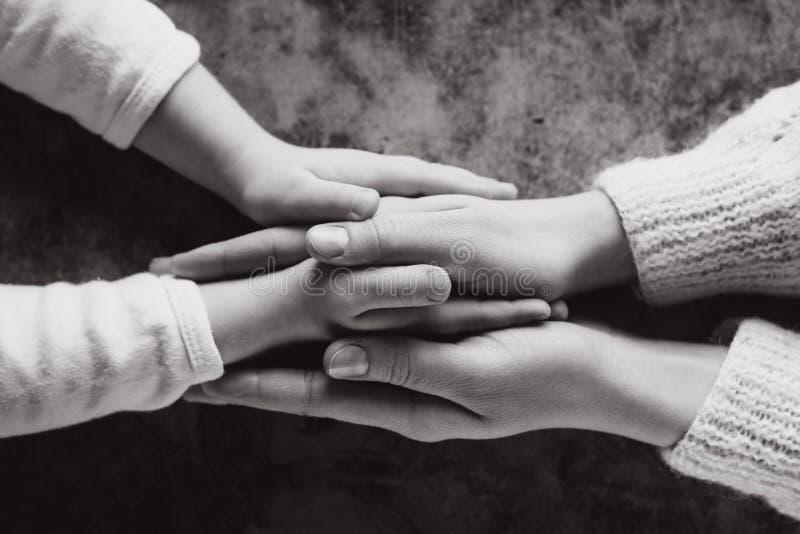 Punto di vista alto vicino della famiglia che si tiene per mano, bambino sostenente preoccupantesi amoroso della madre Mano amica immagine stock libera da diritti