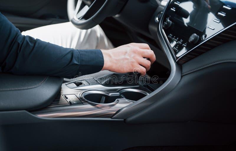 Punto di vista alto vicino di un giovane che conduce un'automobile Inizi un viaggio di affari Prova su strada una nuova auto immagini stock libere da diritti