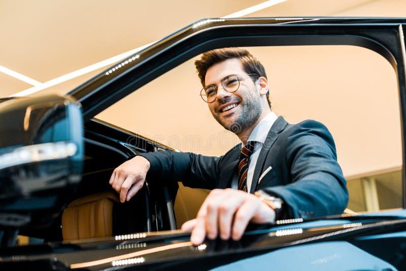 punto di vista di angolo basso dell'uomo d'affari felice in occhiali che posano vicino all'automobile immagini stock