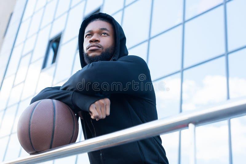 punto di vista di angolo basso dello sportivo afroamericano pensieroso fotografie stock