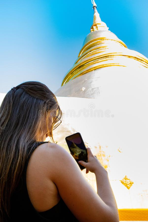 Punto di vista di angolo basso di una donna che prende le immagini della pagoda tailandese bianca e dorata immagine stock