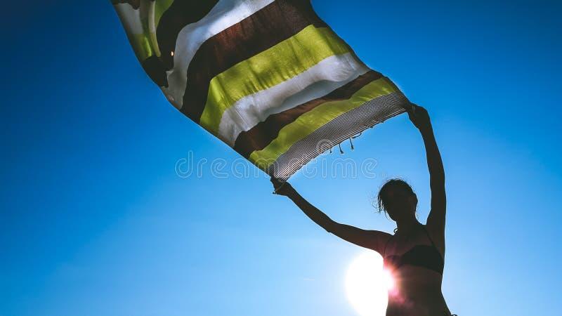 Punto di vista di angolo basso di una donna che tiene un tessuto del perizoma su nell'aria per lasciarla asciutta nel vento immagini stock