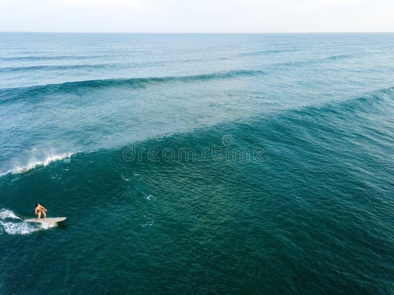Punto di vista del fuco della donna che pratica il surfing da solo immagini stock