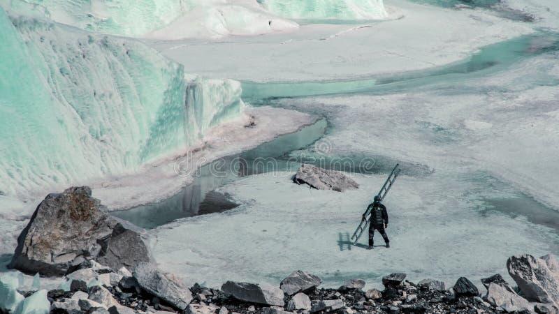 Punto di vista del paesaggio dello scalatore che cammina sul ghiaccio vicino al campo base di Everest fotografia stock