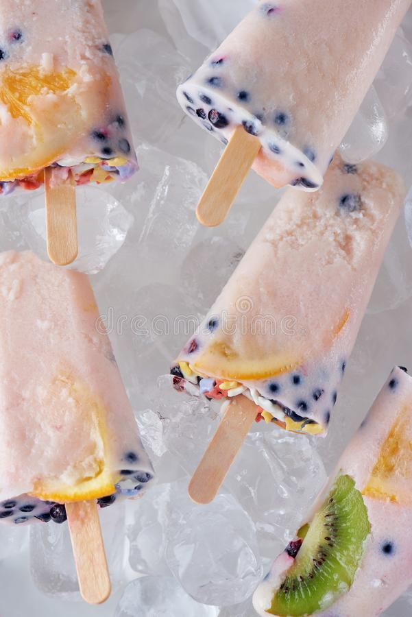 punto di vista del primo piano dei ghiaccioli casalinghi gastronomici con i frutti e delle bacche su ghiaccio fotografia stock