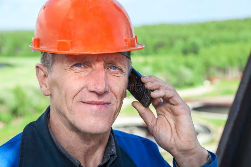Punto di vista del primo piano del lavoratore manuale senior in elmetto protettivo arancio che rivolge al telefono immagine stock libera da diritti