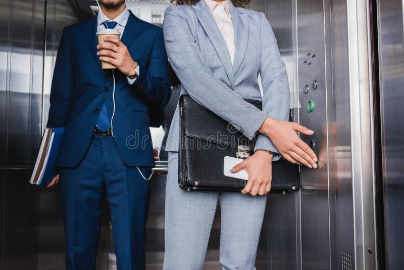 Punto di vista del primo piano della donna di affari che spinge bottone in elevatore dall'uomo in cuffie immagine stock libera da diritti
