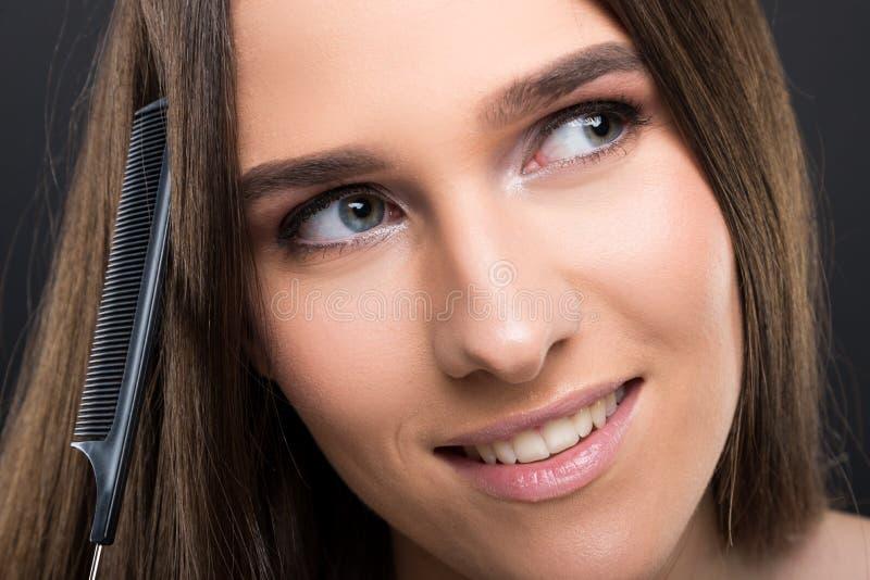 Punto di vista del primo piano della donna che pettina i suoi capelli lunghi fotografia stock