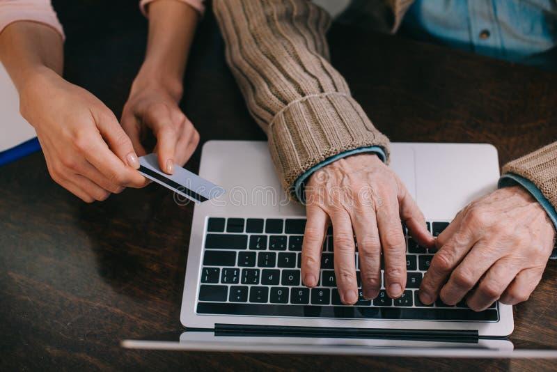 Punto di vista del primo piano della donna e dell'uomo più anziano che usando computer portatile e la carta di credito fotografia stock libera da diritti