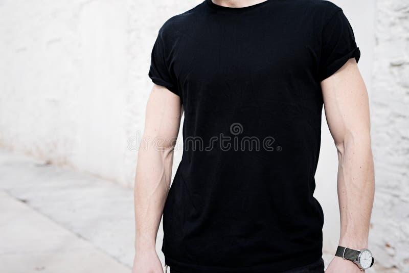 Punto di vista del primo piano di giovane uomo muscolare che porta maglietta nera ed i jeans che posano fuori Parete bianca vuota fotografia stock
