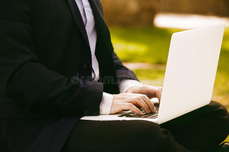 Punto di vista del primo piano di giovane uomo d'affari in formalwear che scrive sulla tastiera del computer portatile mentre sed immagini stock libere da diritti