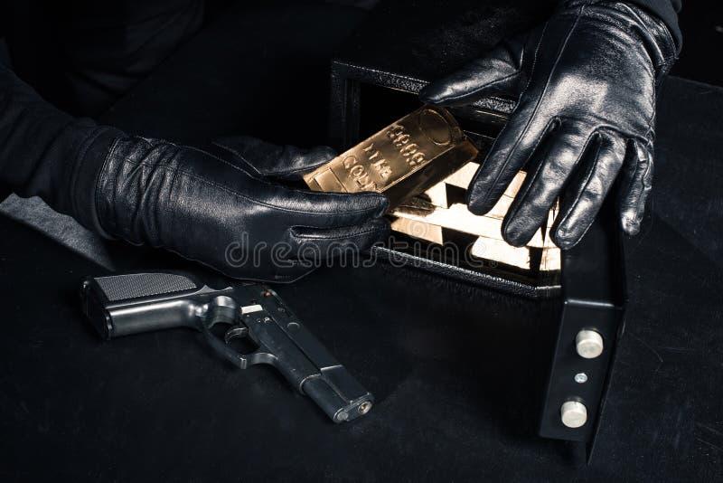 Punto di vista del primo piano del ladro con la pistola che prende le barre di oro fotografia stock