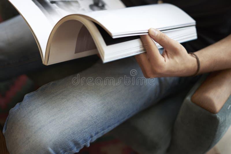 Punto di vista del primo piano di una tenuta della mano dell'uomo che legge rivista di moda moderna fotografia stock libera da diritti