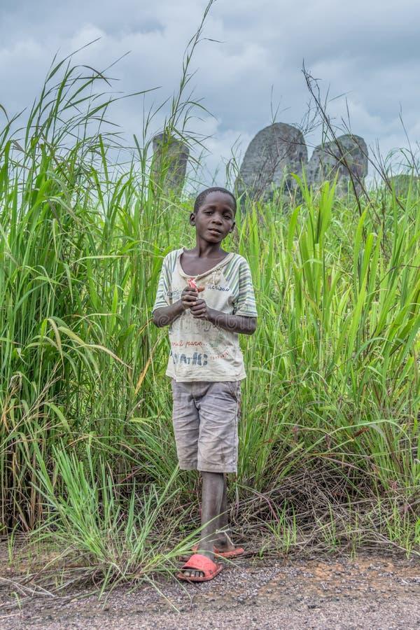 Punto di vista del ragazzo africano povero, paesaggio molto espressivo e tropicale come fondo immagine stock libera da diritti