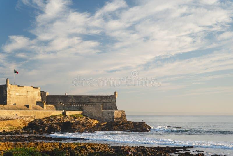 Punto di vista del san Julian Fortress con la torre del faro da Praia de Carcavelos, Portogallo fotografia stock libera da diritti