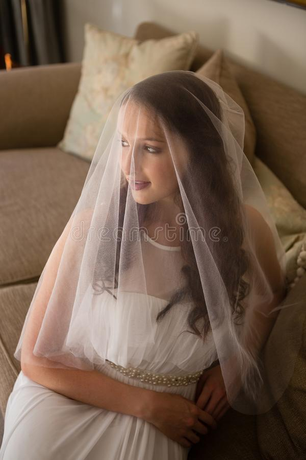 Punto di vista dell'angolo alto di bella sposa in vestito da sposa che si siede sul sofà immagini stock libere da diritti