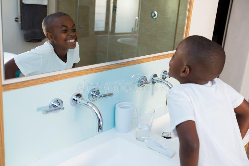 Punto di vista dell'angolo alto del ragazzo che serra i denti mentre esaminando specchio fotografie stock