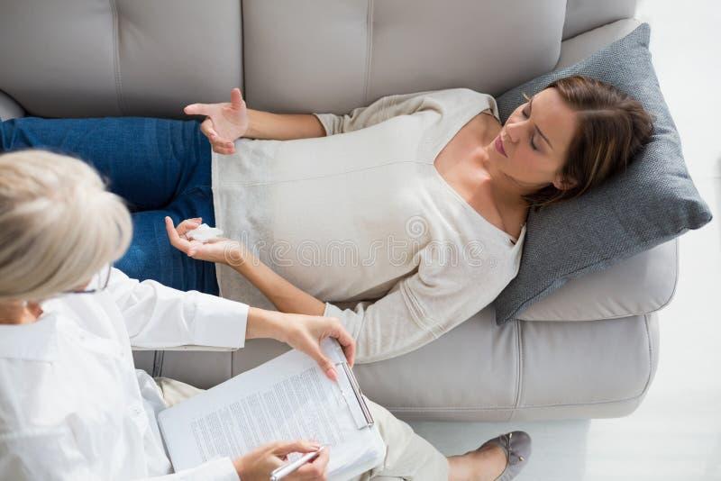 Punto di vista dell'angolo alto della donna che si trova sul sofà dal terapista immagine stock libera da diritti