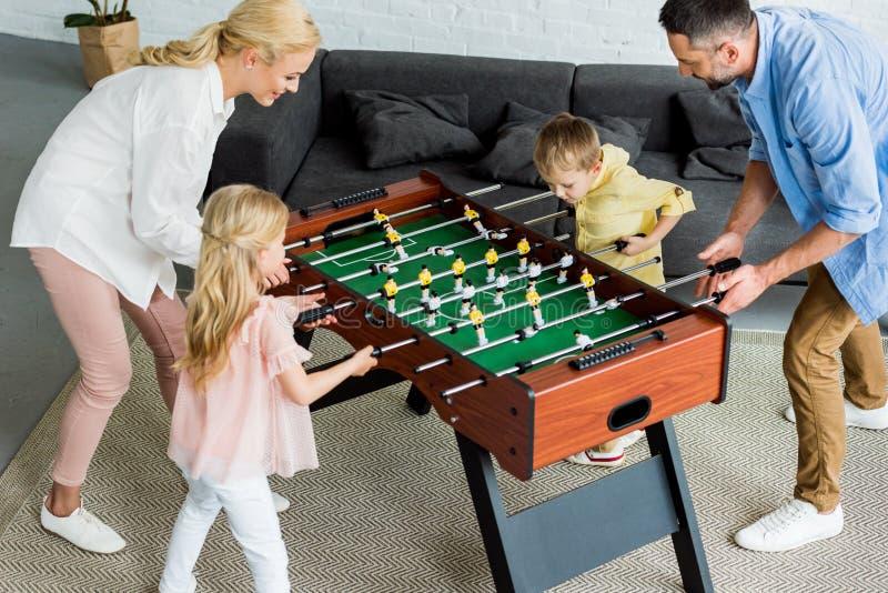 punto di vista dell'angolo alto della famiglia felice con due bambini che giocano insieme calcio-balilla fotografie stock libere da diritti
