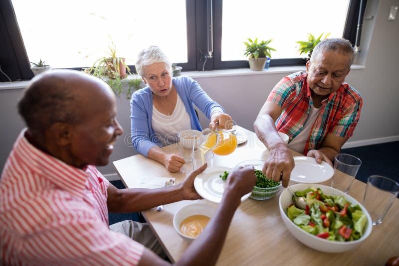 Punto di vista dell'angolo alto della gente senior che mangia insalata e succo immagine stock libera da diritti