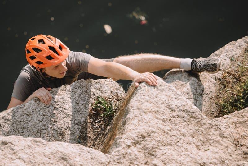 punto di vista dell'angolo alto della viandante maschio messa a fuoco nella scalata protettiva del casco immagini stock