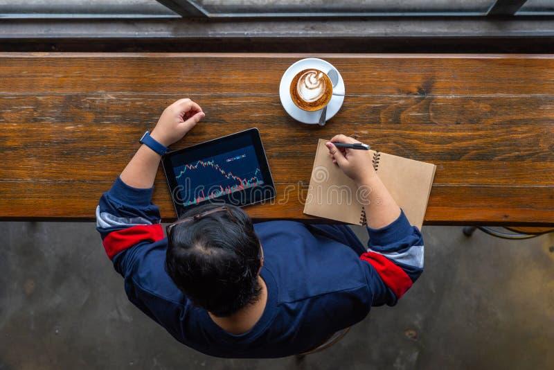 Punto di vista dell'angolo alto dell'investitore asiatico che controlla mercato azionario sulla compressa fotografia stock