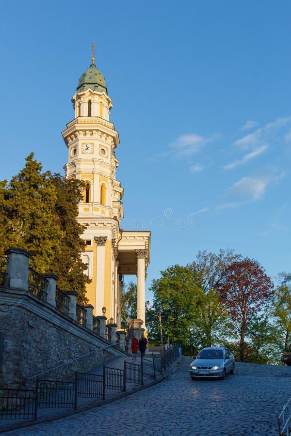 Punto di vista della chiesa, degli alberi, dell'automobile e delle coppie la gente durante il tramonto, cielo blu, Uzhgorod, regi immagini stock