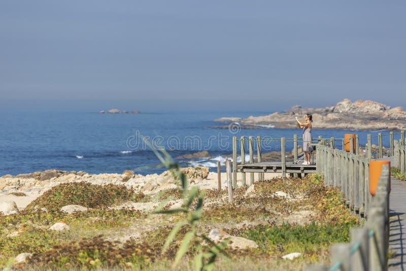 Punto di vista della donna che prende le immagini sul passaggio pedonale, sulla spiaggia e sul mare di legno pedonali As immagine stock