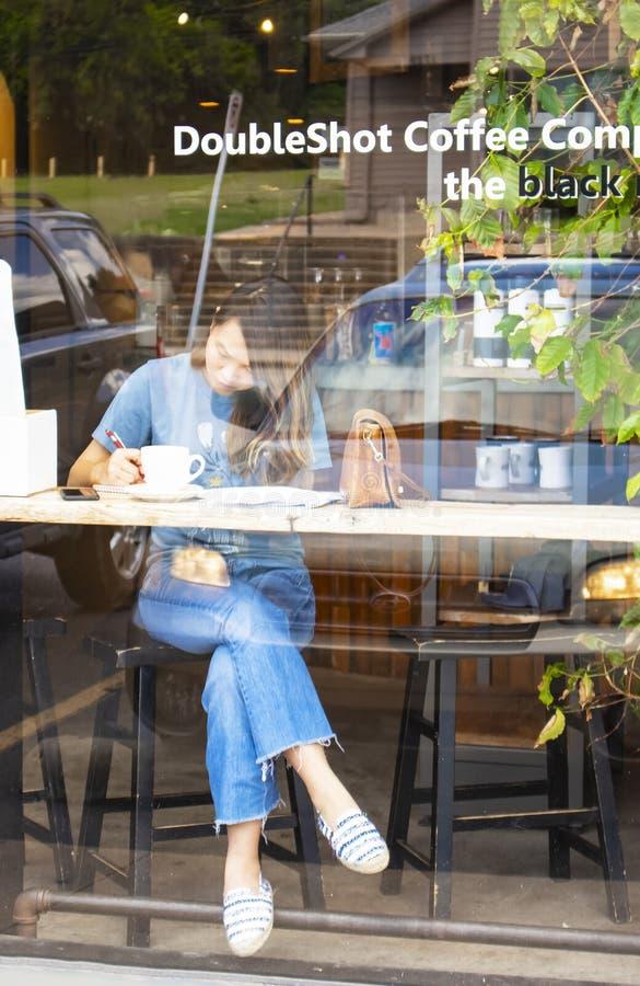 Punto di vista della ragazza nella finestra della caffetteria che lavora al lavoro di ufficio con il telefono che pone colpo vici immagine stock libera da diritti