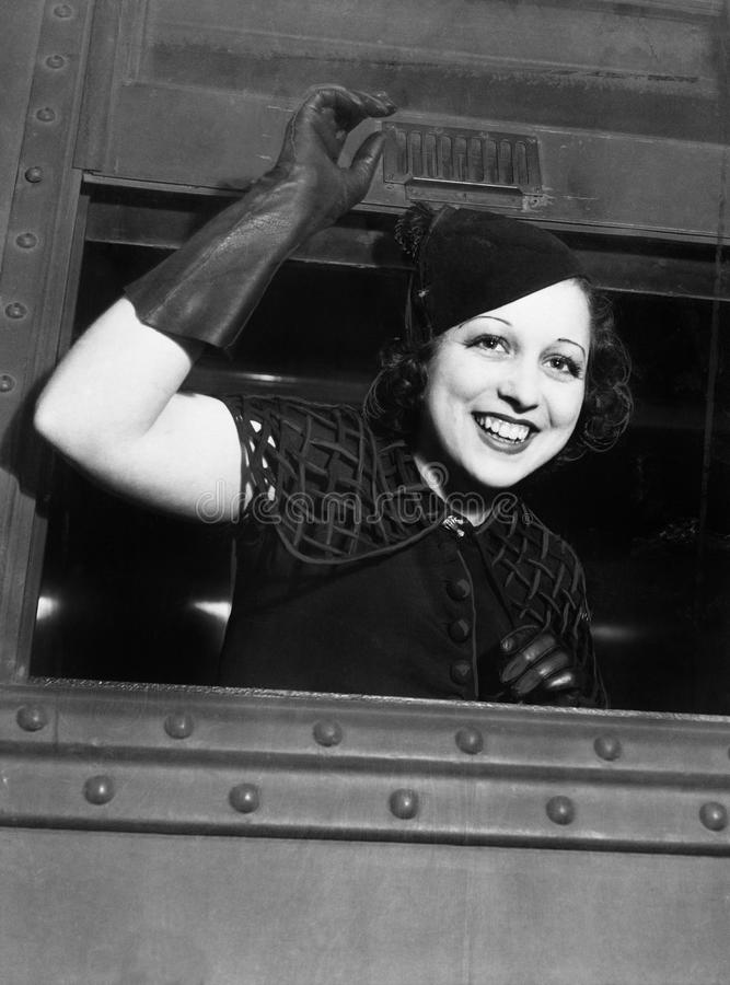 Punto di vista di angolo basso di una giovane donna che guarda attraverso la finestra di un treno e sorridere (tutte le persone r fotografia stock libera da diritti
