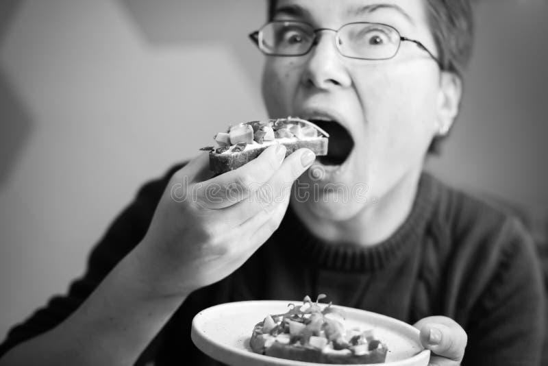 Punto di vista divertente di Upclose della donna caucasica che mangia il pane tostato dell'avocado che esamina macchina fotografi fotografia stock