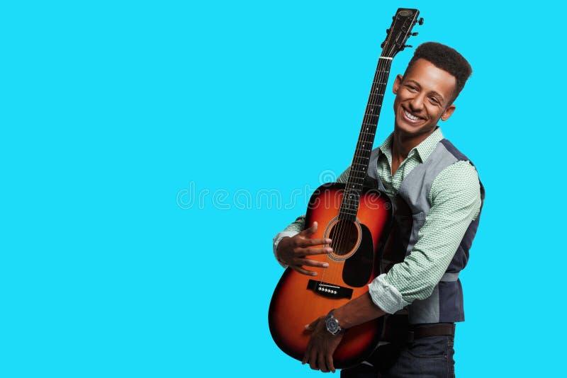 Punto di vista frontale di un giovane della corsa mista di felicità con la chitarra nelle sue armi, giocatore su fondo blu, spazi fotografia stock