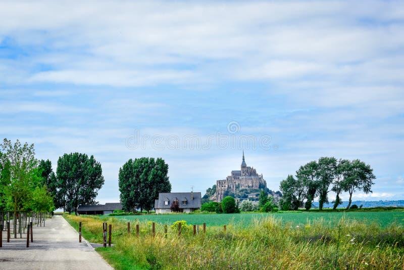 Punto di vista generale di Mont Saint Michel, Francia Percorso, terreno coltivabile ed alberi Cielo blu come spazio per testo fotografia stock