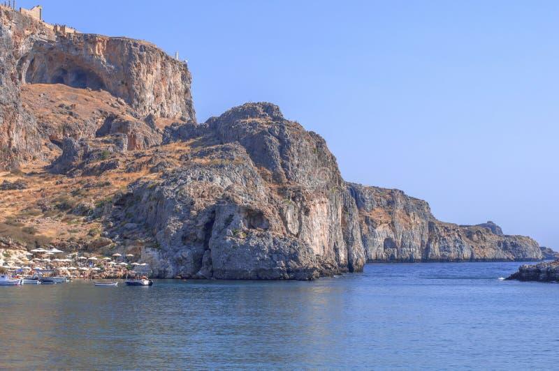 Punto di vista inferiore della scogliera di estate di Rhodes Acropolis di Lindos con il mare fotografia stock