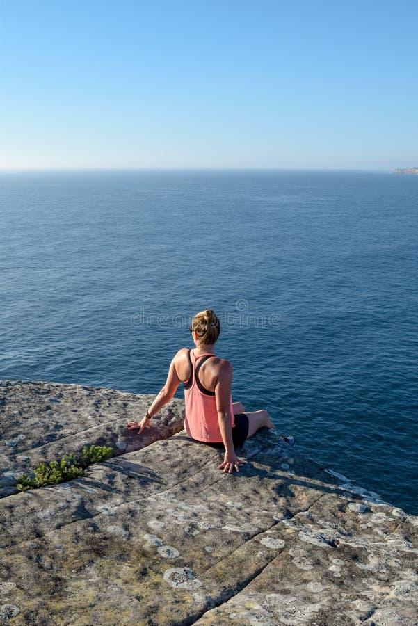 Punto di vista di mattina di giovane viandante femminile che si siede su una roccia alla testa del nord, un promontorio in virile fotografia stock