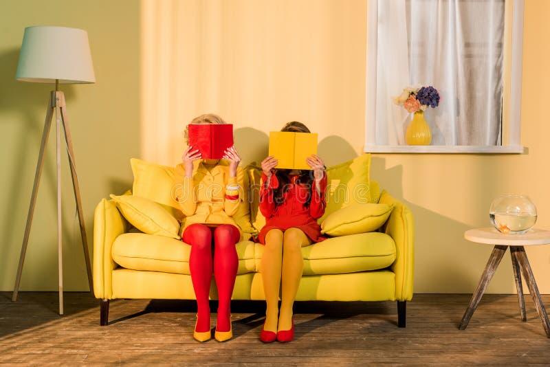 punto di vista oscurato delle donne in retro abbigliamento con i libri che si siedono sul sofà giallo all'appartamento luminoso,  fotografie stock