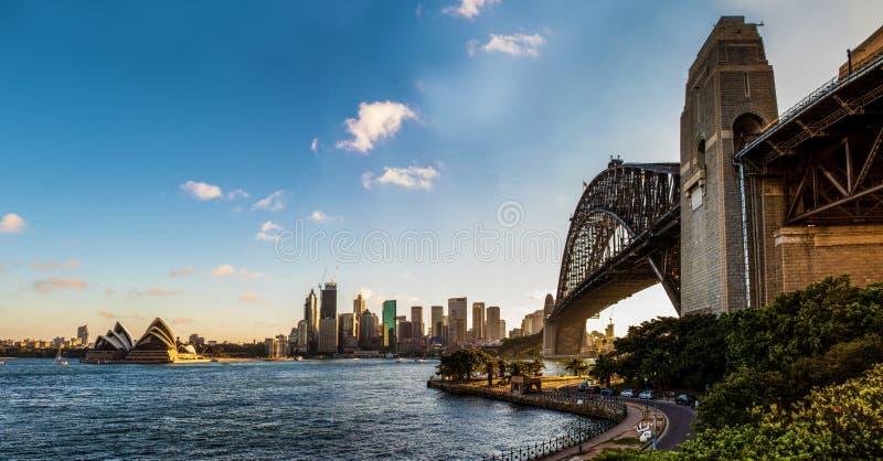 Punto di vista panoramico di Sydney Harbour Bridge, l'orizzonte della città e del teatro dell'opera con un bello cielo blu immagine stock