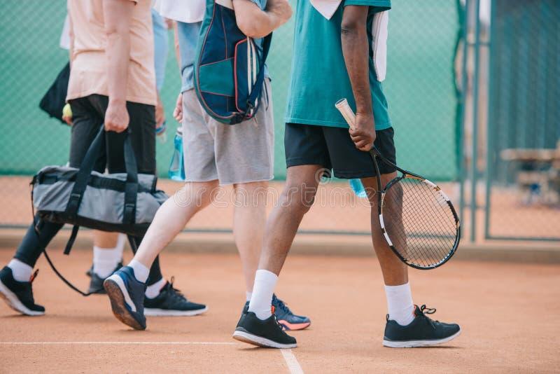 punto di vista parziale degli uomini anziani multiculturali con la camminata dell'attrezzatura di tennis fotografia stock libera da diritti